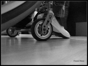 Danny Ruiz--floor view of wheelchair wheels and side of foot in sneaker.