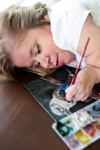 Katherine Kilimitas has blonde hair and is wearing a white shirt. She is laying on her right side as she paints a bird with her left arm. She is a watercolor artist.
