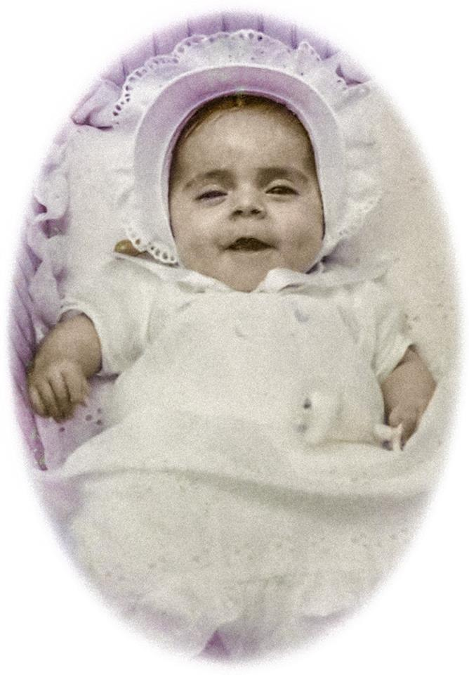 Nathasha when she was about 6 months old in a baby bonnet and white baby gown.