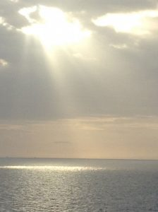 Sunshine streaming through holes in the clouds down to ocean waters.