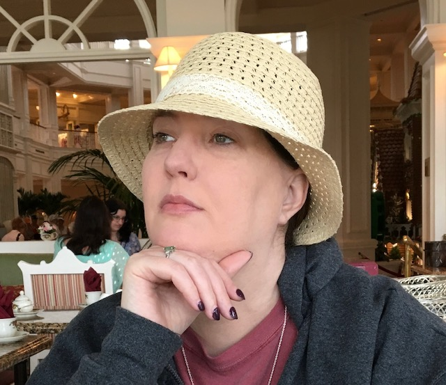 Emily Fitzgerald is a theatrical artist. She is wearing a creamy colored sun hat. She is sitting in a cafe and looking out to her right. Her right hand is under her chin. She is wearing a ring with a precious stone in it. Audacitymagazine.com