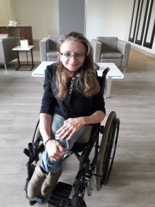 Marelise Prinsloo Jacob sitting in her manual wheelchair. Her legs are crossed and she is in a lobby with two chairs behind her.