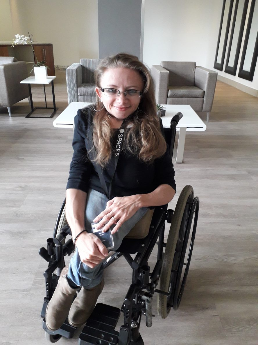 Female with osteogenesis imperfecta sits in her manual wheelchair. She is wearing glasses and has her legs crossed.