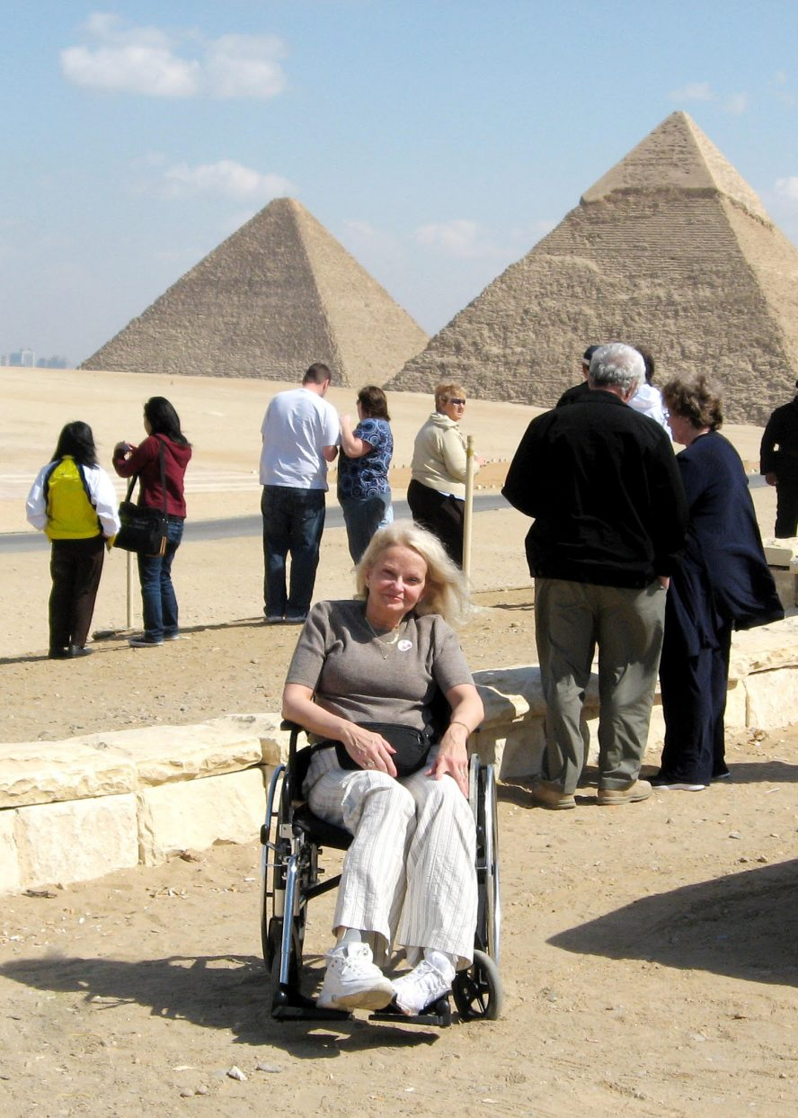A woman with silver blonde hair sits in her manual wheelchair in front of two Eqyptian Pyramids.
