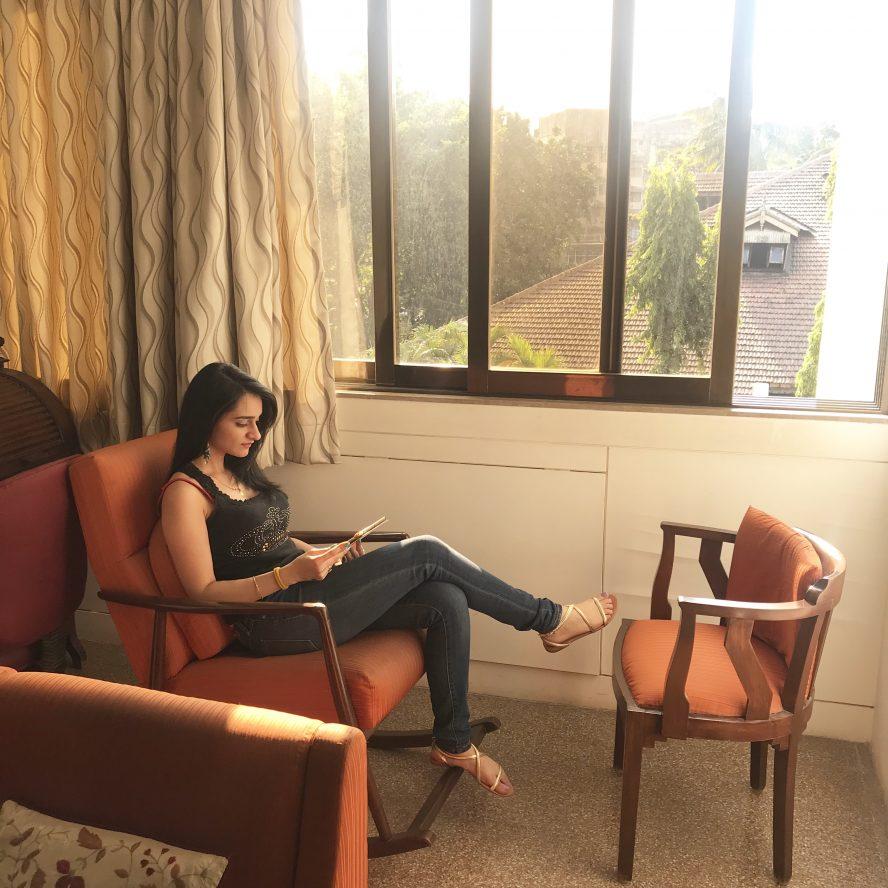 Rhea, a female sits reading in a chair.