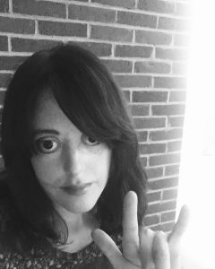 Black and white photo of a white female with long dark hair, parted to the side. She is making the I LOVE YOU sign language sign with her hand. AudacityMagazine.com