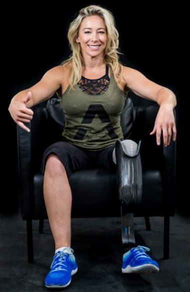 TIna Hurley, a blonde haired woman sitting in sports clothing. She has a prosthetic left leg
