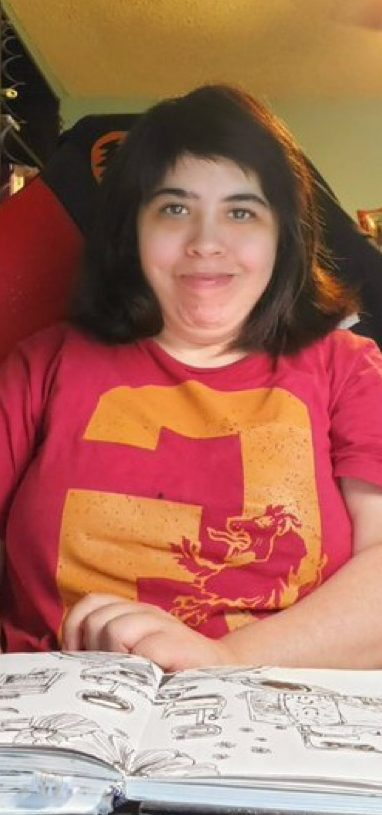 Renee Aguirre is smiling at the camera. She has shoulder length brown hair. She has a sketch book open with her drawings. She is wearing a red and orange t shirt. Renee is an artist.