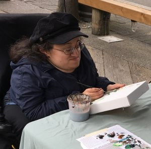 Athena Cooper is looking down at her canvas. She is painting with her right hand. She is wearing a black soft baseball hat. Athena is petite. She is sitting in her motorized chair. She is wearing glasses. Her hair is dark brown and a bit passed the shoulder.