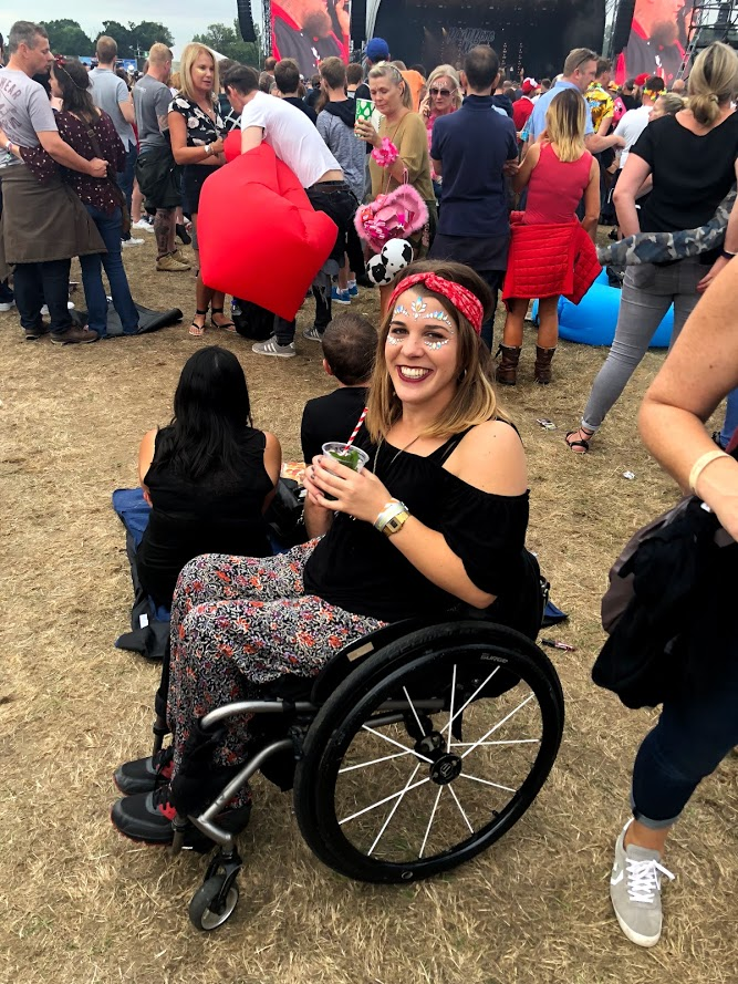 Sophie sitting in her wheelchair at an outdoor event